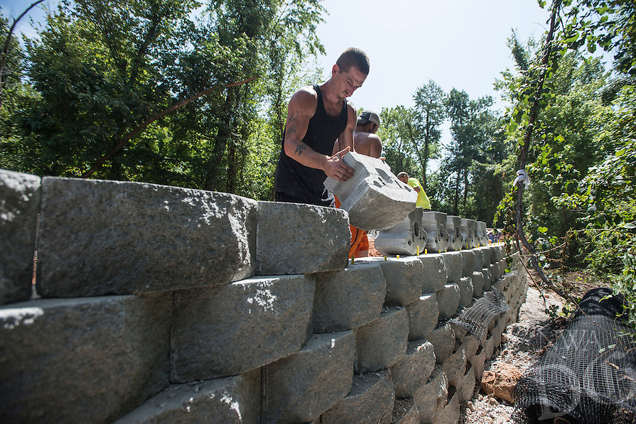 STAFF PHOTO ANTHONY REYES &bull; @NWATONYR<br /> Jason Leftwich, with Mayes Masonry, builds a decorative retaining wall Wednesday Aug. 20, 2014 near Lake Springdale. The wall will support part of the Razorback Greenway trail connection to the Lake Springdale trail. Each block weighs 90 pounds and a crew has built 420 feet of retaining wall reaching as much as seven feet tall in places.