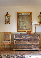 The pristine white walls and painted panelling of the living room are an effective backdrop for a collection of giltwood furniture left in a romantically shabby and unrestored condition
