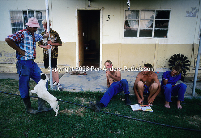 ORANIA, SOUTH AFRICA - DECEMBER 13: White farm workers relaxes outside their rented house after working all day in the fields in Orania, an all white Afrikaner community on December 13, 2003 in the Northern Cape province, South Africa. Many young men from all over South Africa come to Orania to work. Orania was founded in 1991 and bought by descendants of Hendrik Verwoerd, the architect of Apartheid. It is run as a private town only accepting whites. About 600 Afrikaners lives in the village where they celebrate their culture and keep traditions alive. They have chosen not to live in today's South Africa; a country run a black government. (Photo by Per-Anders Pettersson)
