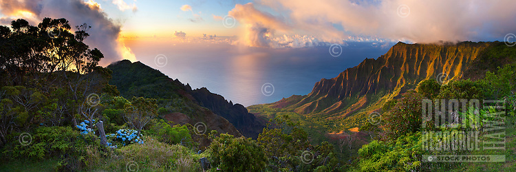Kauai's Kalalau Valley in all its colorful glory.  A summer's sunset illuminates the valley's undulating walls as a rain cloud passes by below.