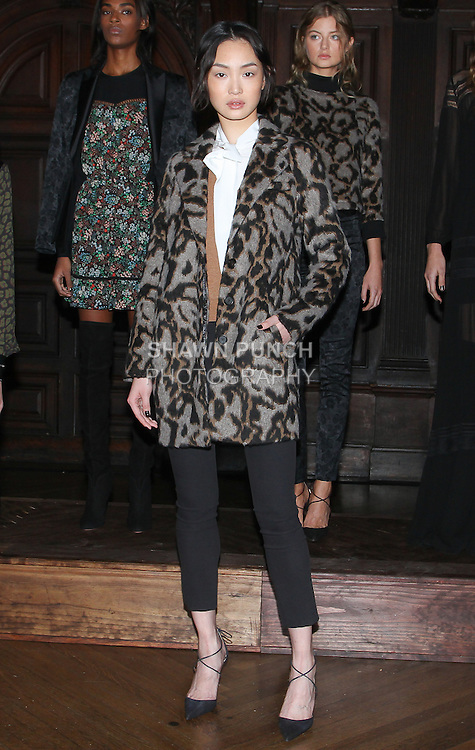 "Model August poses in a leopard mohair jacquard cocoon coat, haystack cashmere Trompe l'Oeil tie neck sweater, and black stretch techno twill cropped barely there flare, from the Veronica Beard Fall 2016 ""Gypsy Caravan"" collection presentation, at the Highline Hotel on February 15 2016, during New York Fashion Week Fall 2016."