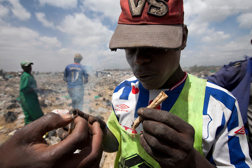13 february 2013 - Dandora dumpsite, Nairobi, Kenya - A Kenyan man lights a marijuana cigarette at the Dandora dumpsite, one of the largest and most toxic in Africa. Located near slums in the east of the Kenyan capital Nairobi, the open dump site was created in 1975 and covers 30 acres. The site receives 2,000 tonnes of unfiltered garbage daily, including hazardous chemical and hospital wastes. It is a source of survival for many people living in the surrounding slums, however it also harms children and adults' health in the area and pollutes the Kenyan capital. Photo credit: Benedicte Desrus