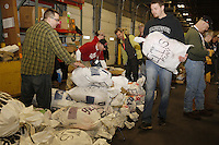 Wednesday, February 13, 2013.  Volunteers sort Mike Ellis's food bags prior to weghing them during the musher's food drop day at Airland Transport in Anchorage.  Iditarod 2013