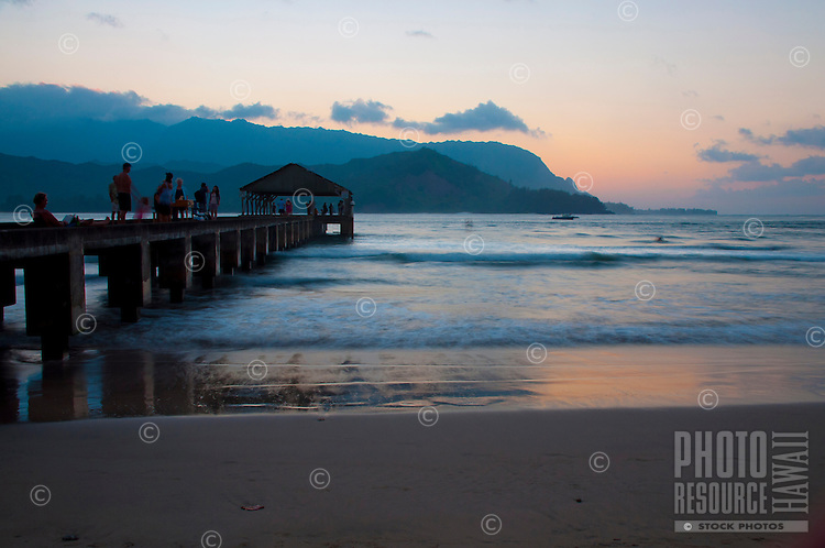 Relaxing on the pier at Hanalei Beach Park on the North Shore of Kauai, with a golden-glow sunset lighting up the water's edge and the sky over Na Pali.