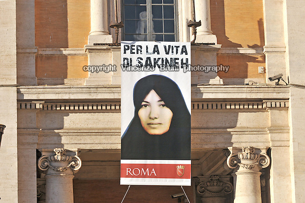 A placard showing a portrait of Iranian woman Sakineh Mohammadi Ashtiani is hung outside the Palazzo dei Conservatori on Campidoglio town hall in Rome on September 2, 2010, as part of a campaign against her brutal execution by stoning sentenced by an Iranian court.
