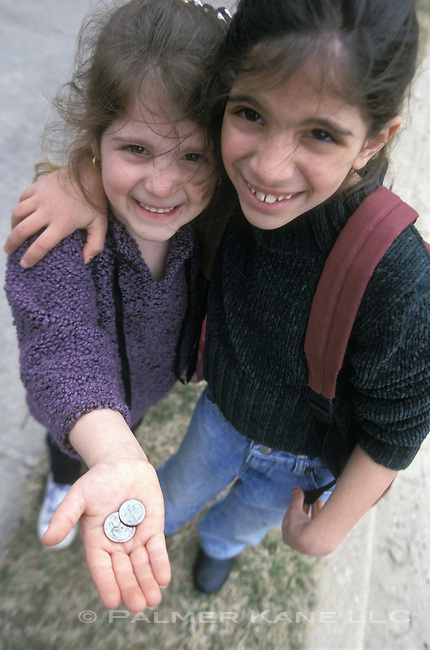 Two girls standing together, one girl holding small change in her hand.