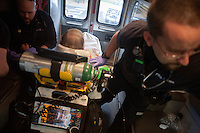 Vahe Ender (right) and Derek Jordan of Pro EMS care for a patient in an ambulance in Cambridge, Massachusetts, USA.  The patient had been experiencing shortness of breath, and paramedics administered care in his home and the ambulance before taking him to a hospital.  The company analyzes 100% of their calls, even if the patient refuses care. After a call, the paramedics and EMTs record all data about the call, including patient demographic information, medicine and care administered, and a narrative of their entire response to the emergency call.  This data is used by hospitals to inform their care of the patient and by Pro EMS to assess the quality of their care and also provide data for predictive models they use to place ambulances throughout the company's service area.  The data may also be used if information about the call will be used in court or insurance investigations.
