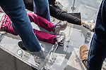 The feet and legs of people standing and lying on the Ledge at the Willis Tower Skydeck, Chicago, IL