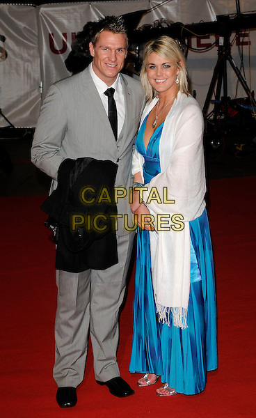 "JEAN DE VILLIERS & GUEST.Attending the ""Invictus'"" UK Film Premiere at the Odeon West End cinema, Leicester Square, London, England, January 31st, 2010. .arrivals full length grey gray suit black tie blue long maxi dress print white pashmina wrap shawl.CAP/CAN.©Can Nguyen/Capital Pictures"