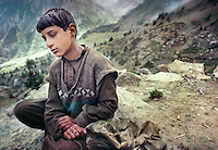 A young shepherd takes a break at his high altitude pasture. Trekking in Basho Valley..Karakoram mountain range, Baltistan, Pakistan.