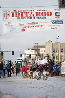 Seth Barnes and team leave the ceremonial start line with an Iditarider at 4th Avenue and D street in downtown Anchorage, Alaska during the 2015 Iditarod race. Photo by Jim Kohl/IditarodPhotos.com