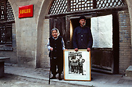 September, 1985. Shaanxi Province, China. In this house lived Mao Zedong starting 1937 for few years and now this couple live in this house and keep the memory of Mao alive for the visitors. They proudly show a picture of Mao in front of the same house with two officers of the Red Army.