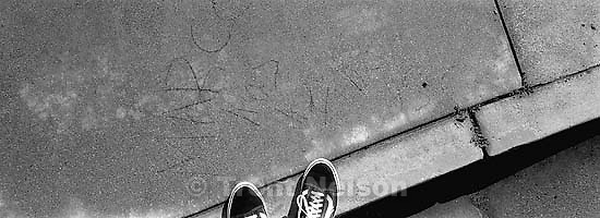 Trent feet and &quot;Marco has a fine ass&quot; scrawled in sidewalk.<br />