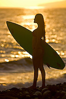 A girl with a surfboard is silhoutted by the setting sun at Olowalu, Maui.