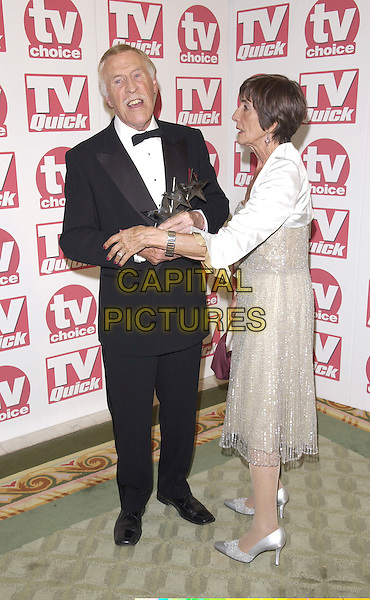 BRUCE FORSYTH & JUNE BROWN.Arriving at the TV Quick & TV Choice Awards,.Dorchester Hotel, Park Lane,.London, 5th September 2005.full length tuxedo black tie silver dress high heel shoes arms fight.www.capitalpictures.com.sales@capitalpictures.com.© Capital Pictures.