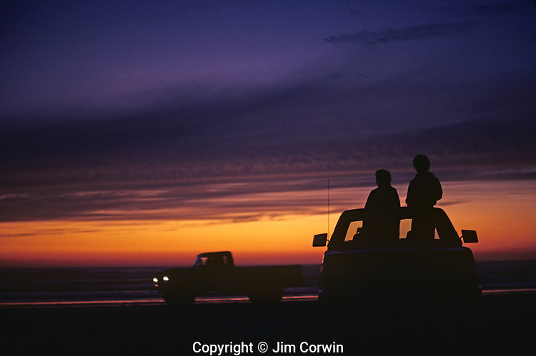Silhouetted couple in back of a pick up truck standing and looking at sunset at the beach Ocean Shores Washington State USA.