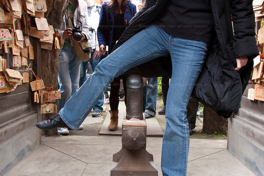 Women walk over an iron phallus in the grounds of Wakamiya Hachiman gu shrine in the hope of sexual and reproductive health during the Kanamara matsuri, Kawasaki Daishi, Japan April 5th 2009