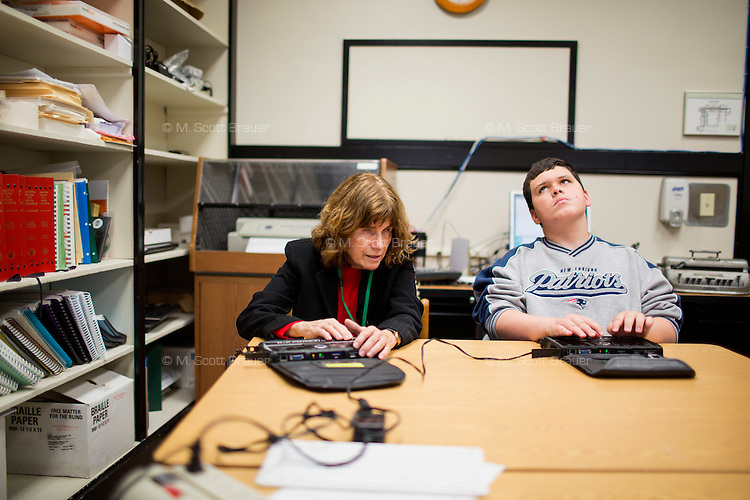 Michael Daggett, 19, (in gray) uses a BrailleNote Apex Notetaker in computer class with Kate Crohan, Teacher of the Visually Impaired in the Secondary Program at Perkins School for the Blind in Watertown, Massachusetts, USA, on Tues., Oct. 15, 2013. The Apex has wifi capabilities and works as a word processor, web browser, calculator, and email device. Daggett will be at Perkins for two years in training for personal independence, and has been at the school for one year already. Daggett has been using the Apex Notetaker for about a week. Crohan was helping Daggett learn some of the functions of the email application on the device, which is controlled through the braille keyboard buttons at the top. Emails and other documents are displayed in braille across the bottom row of the device.