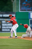 Batavia Muckdogs shortstop Dalvy Rosario (17) throws to first base as Wilmer Perez (20) slides in during a NY-Penn League game against the Auburn Doubledays on June 14, 2019 at Dwyer Stadium in Batavia, New York.  Batavia defeated 2-0.  (Mike Janes/Four Seam Images)