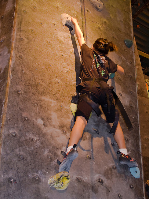girl climbing rock wall at indoor climbing gym, Colorado