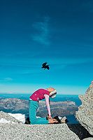 Martina Cufar practicing yoga high in the Alps with an Alpine Choughs (Pyrrhocorax graculus) flying above her head.