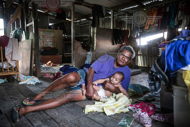 Sei Kawapa, 60, takes care of his four month old grandson Fiapule in their house in Teone village. Sei's house was hit by tidal surges when Cyclone Pam hit Tuvalu in March 2015.  <br /> Sei recalls: 'Big waves hit our house, one of them destroyed a wall. It was unexpected, we were not prepared. It's good that I was near my grandson when the water came inside. I grabbed him and lifted him up. Otherwise he might have drowned or even taken by waves to the ocean, I don't know...'