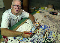 BROOKHAVEN, PA - AUGUST 14:  Al Holcombe, 65, of Brookhaven, Pennsylvania, creates maps made from U.S. license plates in his workshop, Aug. 14, 2002, in Brookhaven, Pennsylvania. Holcombe cuts the plates into the shape of the respective states, the sodders them together to form a United States map. (Photo by William Thomas Cain/Getty Images)