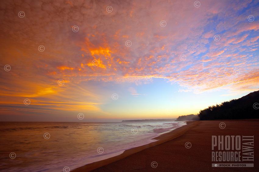 A sunrise opens up the sky in golden hues over Lumaha'i Beach, Kaua'i.