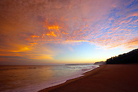 A sunrise opens up the sky in golden hues over Lumaha'i Beach, Kaua'i.