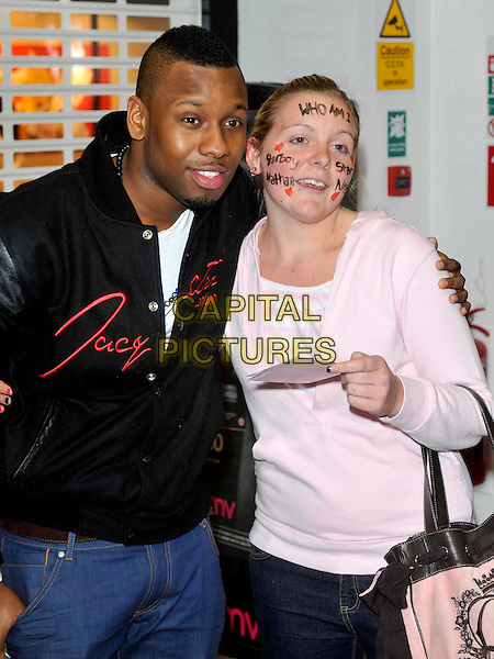 Starboy Nathan .at a signing of his new CD at HMV, Milton Keynes, Bucks, UK, .May 17th 2012..half length black jacket posing with fan face paint writing  .CAP/ROS.©Steve Ross/Capital Pictures.