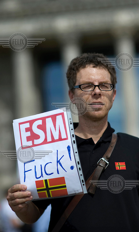 A protestor iholds a poster reading 'ESM Fuck!' at a demonstration against the EU fiscal pact outside the Reichstag in Berlin. Bundestag members are set to vote on ratification of the fiscal pact and the ESM (European Stability Mechanism) inside the parliament. Left wing party Die Linke are past of the protest.