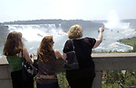 Niagara Falls, Ontario, Canada - 01 August 2006---Tourists / visitors / women overlooking Niagara River with the Horseshoe Falls (ri), on the Canadian side and the American Falls (le), on the United States' side---nature, landscape, people---Photo: © HorstWagner.eu