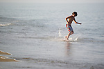 A young boy enjoys skimboarding on the beach in Duck during a family vacation to the Outer Banks town of Duck, North Carolina.  Duck is located on the north end of the Outer Banks and has experienced exponential growth over the past ten years. Duck is now a thriving year-round town as well as vacation destination. (Photo by Artisan Photography Group/Chris English)