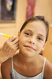 FRENCH POLYNESIA, Tahiti. Fiona getting her ears pierced in Papeete, Tahiti.