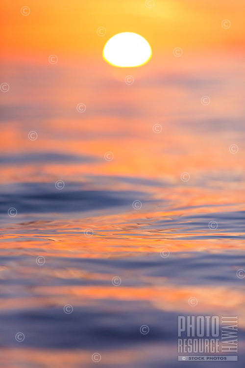 A close focus image of the calm ocean reflecting a sunset near Maui.
