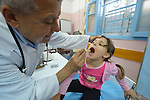 Dr. Habeeb Attallah examines a young patient in a clinic in Rafah, in the south of Gaza. The clinic is run by the Department of Service for Palestinian Refugees of the Near East Council of Churches, a member of the ACT Alliance, and funded in part by the Pontifical Mission for Palestine.