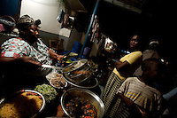 "a woman serves local food at a ""chop house"" while awaiting for the 50th anniversary of their countries' independence in the Jamestown neighborhood in Accra, Ghana on Sunday March 04 2007.."