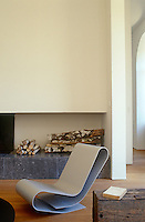 The smoothness of a curved aluminium chair by Maarten Van Severen is accentuated by being arranged in front of  the fireplace in the living room
