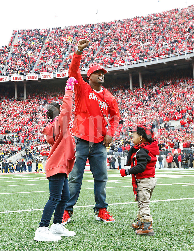 Former Ohio State Buckeyes quarterback Troy Smith celebrates on the field with his kids Taniya, 6, left, and, Troy Jr., 2, right, after being honored during the college football game between the Ohio State Buckeyes and the Michigan Wolverines at Ohio Stadium in Columbus, Saturday morning, November 29, 2014. The Ohio State Buckeyes defeated the Michigan Wolverines 42 - 28. (The Columbus Dispatch / Eamon Queeney)