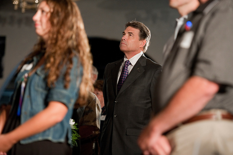 UNITED STATES - AUGUST 14:  Republican presidential candidate Texas Gov. Rick Perry, observes a silence for fallen service members, during the Lincoln Day Dinner hosted by the Black Hawk County Republican Party in Waterloo, Iowa.  Candidates Perry, Rep. Michele Bachmann, R-Minn., and Rick Santorum, addressed the gathering.  (Photo By Tom Williams/Roll Call)