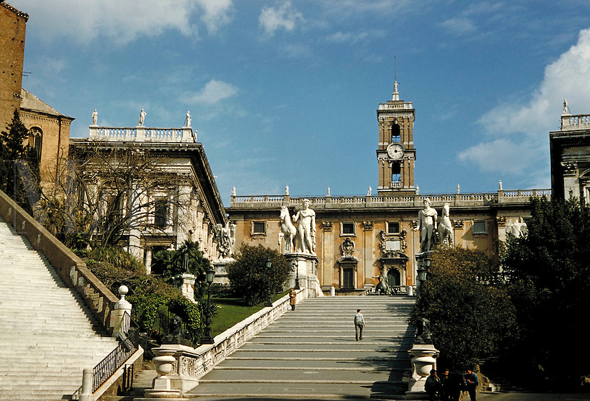 Campidoglio and clock tower at head of broad stairs; heroic statuary; 2 men on stairs and 4 talk at foot. Rome, Italy.