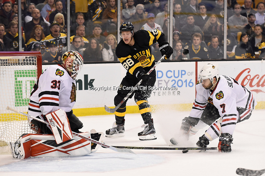 Thursday, March 3, 2016: Boston Bruins left wing David Pastrnak (88) passes the puck between Chicago Blackhawks goalie Scott Darling (33) and defenseman Brent Seabrook (7) during the National Hockey League game between the Chicago Blackhawks and the Boston Bruins, held at TD Garden, in Boston, Massachusetts. Boston defeated Chicago 4-2. Eric Canha/CSM