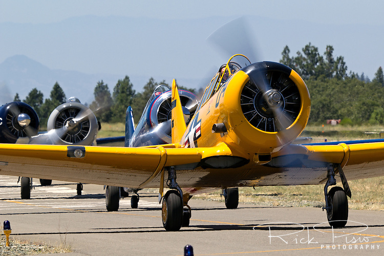 World War II era T-6 Texan trainers taxi down the ramp at the Nevada County Airport.