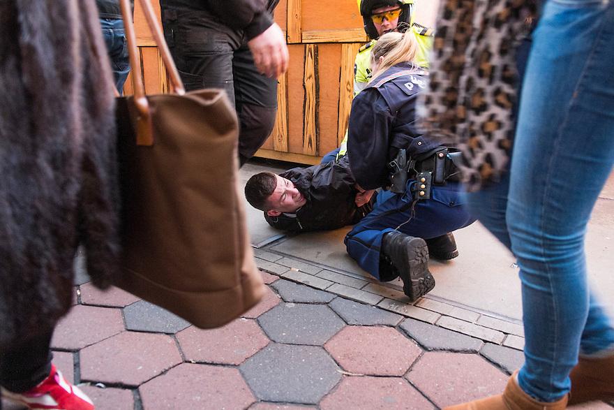 Nederland, Amsterdam, 11 jan 2014<br /> Op het Damrak wordt een verdachte gearresteerd door de politie.  Het winkelend publiek loopt gewoon door.<br /> Foto: Michiel Wijnbergh