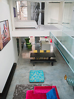 A view from one mezzanine across the atrium to another which contains the only bedroom. A glass bridge connects the two