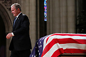 Former President George W. Bush walks past the casket of his father, former President George H.W. Bush, at the State Funeral at the National Cathedral, Wednesday, Dec. 5, 2018, in Washington.  <br /> Credit: Alex Brandon / Pool via CNP