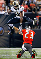 New Orleans Saints wide receiver Brandin Cooks (10) leaps over Tampa Bay Buccaneers defensive back Chris Conte (23) in the second half of an NFL football game in New Orleans, Sunday, Sept. 20, 2015.