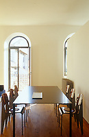 A pristine black steel table surrounded by six plywood chairs in the dining area designed in minimalist style