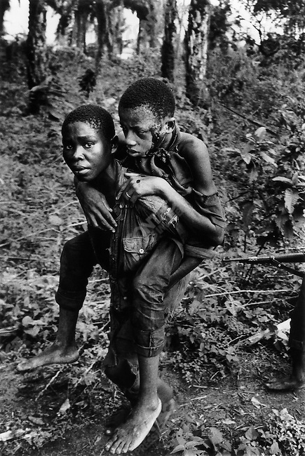 Ibo soldier carrying wounded comrade, civil war, Biafra, Nigeria, April 1968