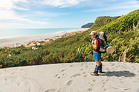 Female tramper on Three Mile Beach near Okarito, Westland Tai Poutini National Park, West Coast, UNESCO World Heritage Area, New Zealand, NZ